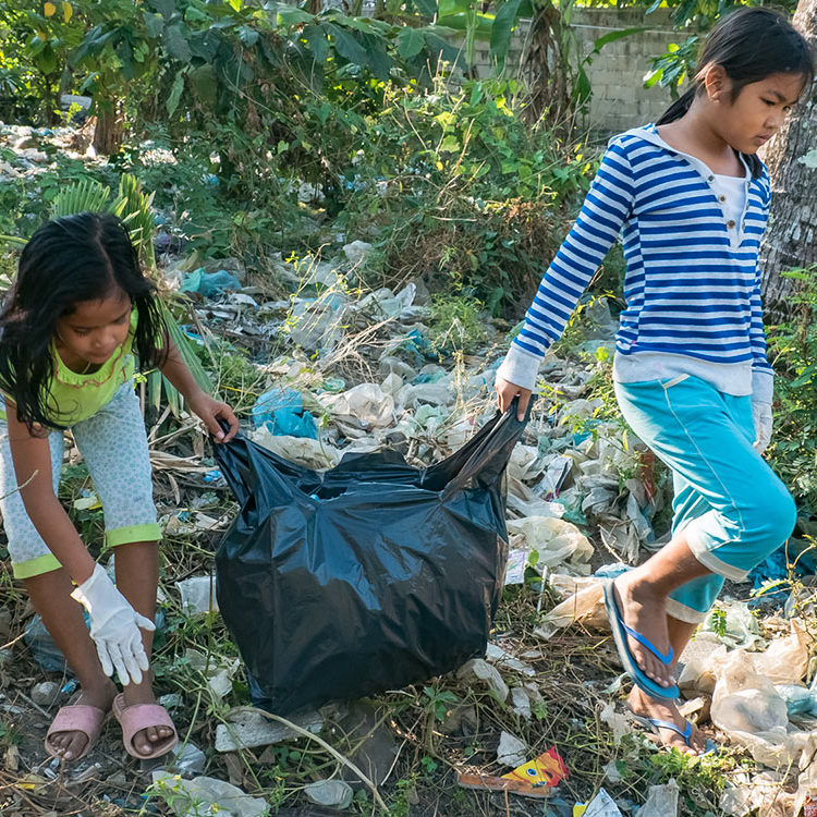 Khmer children are picking up discarded plastic bags near their school, for an ecological and craft courses for underprivileged schoolchildren in Sihanoukville.