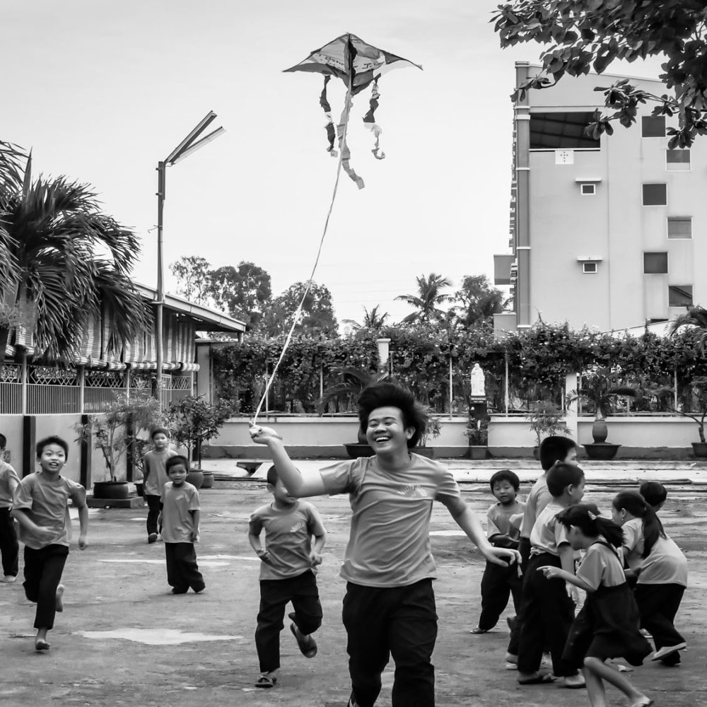Joyful Vietnamese schoolchildren are playing with a homemade kite made with upcycled plastic bags during a fun filled ecological course in Ho Chi Minh City.