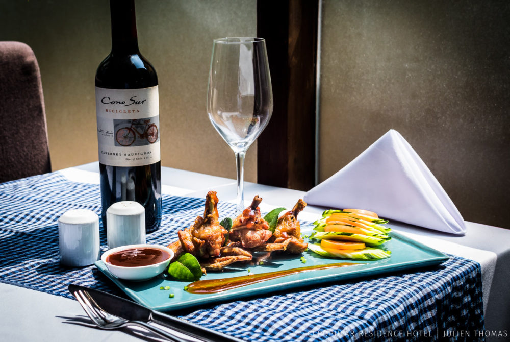 Western dish with chicken wings and vegetables side coming with a bottle of red wine in the restaurant at Popular Residence Hotel, Siem Reap - Cambodia.