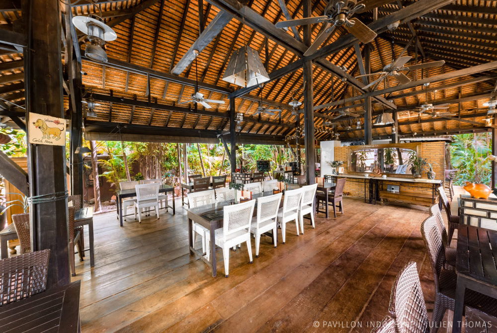 Picturesque open restaurant area with high wooden celling and facing the garden and swimming pool area in Pavillon Indochine, Siem Reap - Cambodia.